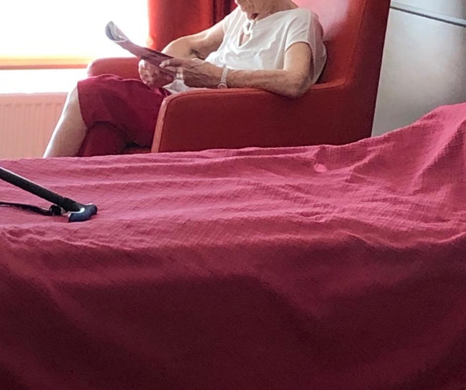 résidente d'EHPAD lisant dans sa chambre